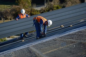man working on a steel roof